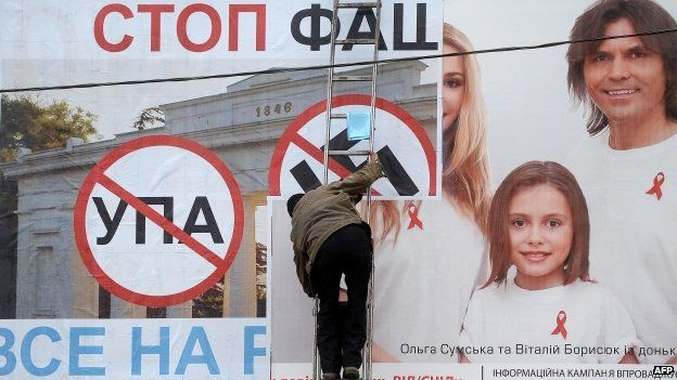 """A man posts a on billboard a poster bearing a Nazi swastika and reading """"Stop Nazism, all to the referendum"""" in the Crimean city of Sevastopol"""