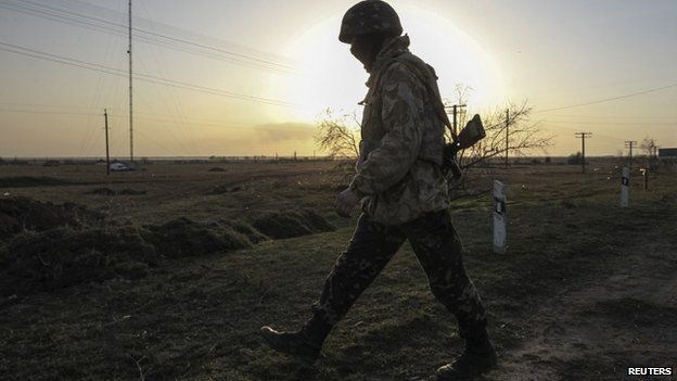 A Ukrainian soldier walks at a checkpoint near the village of Stavki, near the Crimean regional border