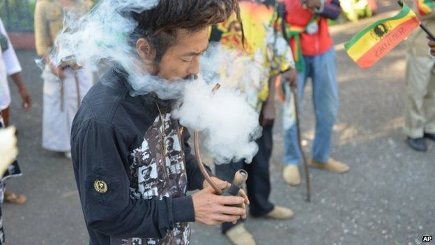 A man smokes a pipe of marijuana outside a museum dedicated to the memory of late reggae icon Bob Marley in Kingston on 6 February 2013