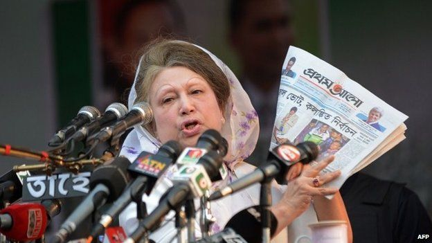 Khaleda Zia holds a Bengali newspaper while addressing a rally in Dhaka on January 20, 2014.