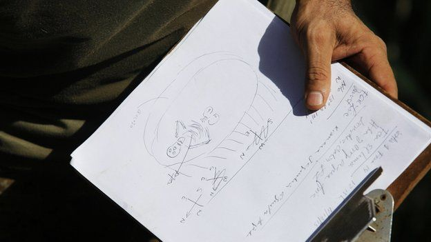 Forensic technician holds a drawing of the position of a human body during an exhumation at a hidden mass grave discovered in Lourdes