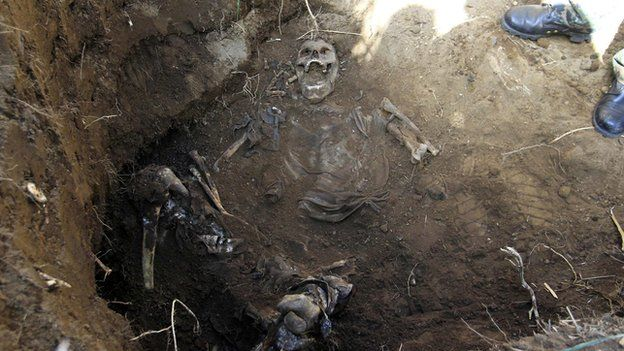 A forensic technician stands next to the remains of a person
