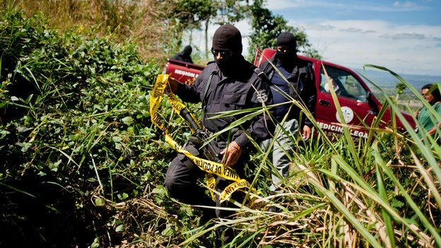 Police investigators secure the site of an unmarked grave