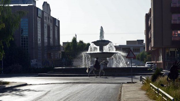 An Afghan man rides his horse past a fountain in the Aino Mena area in Kandahar city