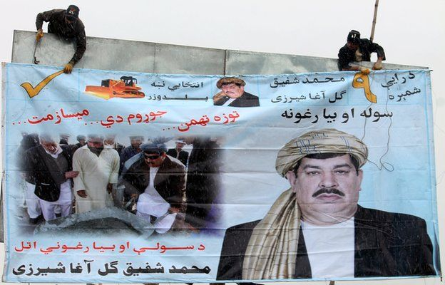 Afghan workers erect an election campaign poster of politician Gul Agha Shirzai in Kandaha