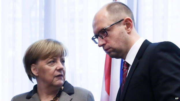 Ukrainian Prime Minister Arseniy Yatsenyuk, right, speaks with German Chancellor Angela Merkel after a signing ceremony at an EU summit in Brussels on Friday, March 21, 2014