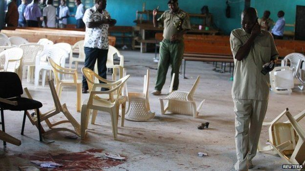 Police officers inspect blood stains on the floor of a church in Likoni. Photo: 23 March 2014
