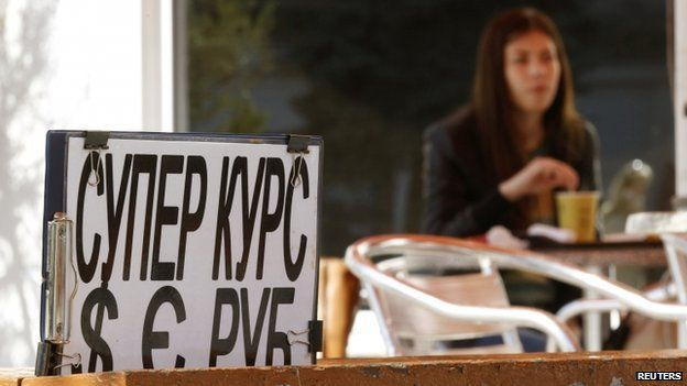 A woman sits in a cafe behind an advertising placard in Sevastopol on 24 March 2014.