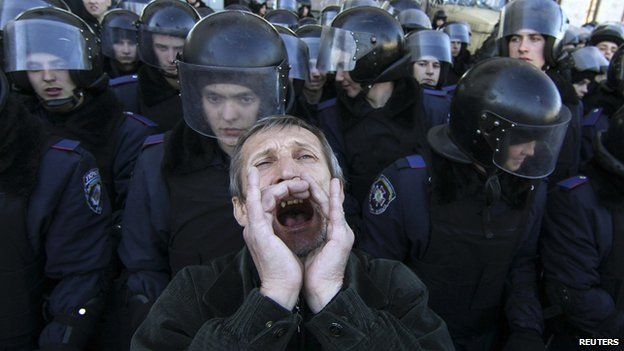 A pro-Russian protester shouts slogans in front of Ukrainian riot police guarding the regional administration building during a rally in central Donetsk on 22 March 2014