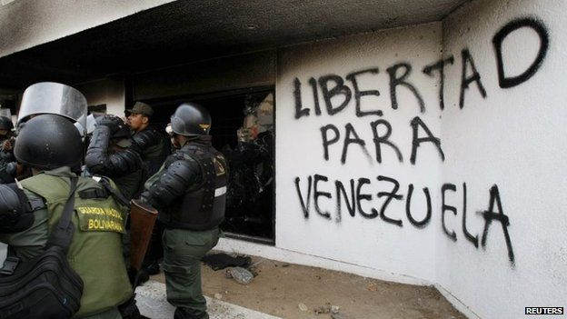 National guards inspect the national electoral headquarters in Maracaibo after a fire which, according to government officials, was set by anti-government protesters on 25 March, 2014