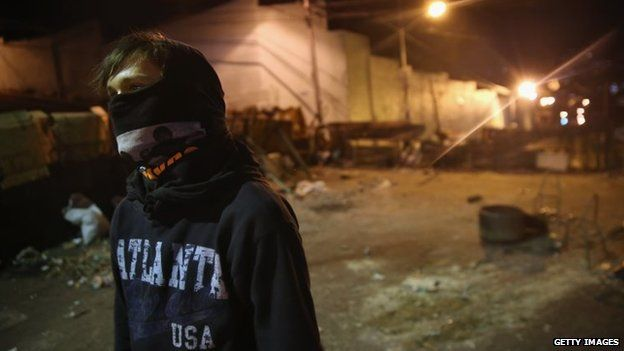 A young protester mans a barricade before dawn on 9 March, 2014 in San Cristobal