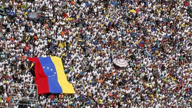 Opposition supporters hold a national flag during a rally against President Nicolas Maduro's government in Caracas on 22 March, 2014