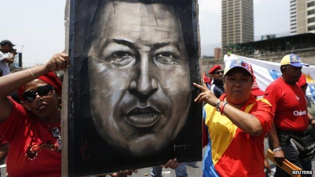 Supporters of Venezuela's late president, Hugo Chavez, hold an image of him as they take part in a rally to commemorate the 20th anniversary of Mr Chavez being freed from jail in Caracas on 26 March, 2014.