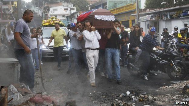 Relatives and mourners carry the coffin of Jimmy Vargas, a student who died during a protest, through a barricade during his funeral in San Cristobal on 26 February, 2014