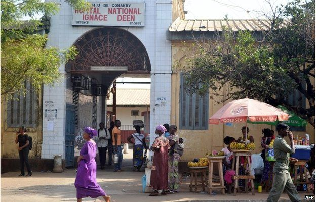People walk in front of the Ignace Deen hospital in Conakry on 27 March