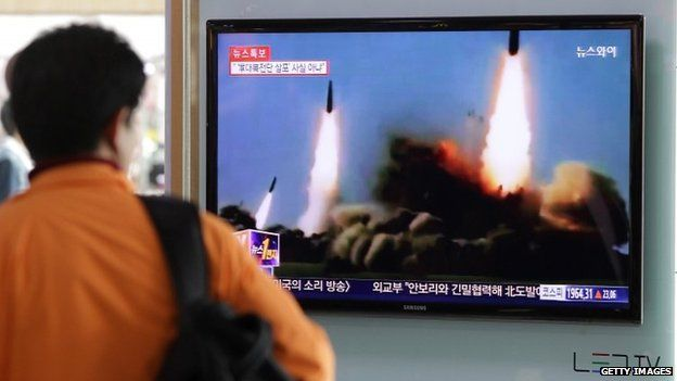 Man watches TV broadcast of North Korean missile launches. 26 March 2014