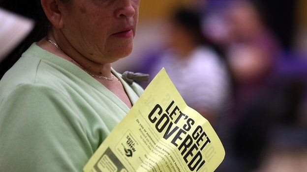 """A woman holds a flier with the words """"let's get covered"""" during a healthcare signup fair in California on 28 March."""