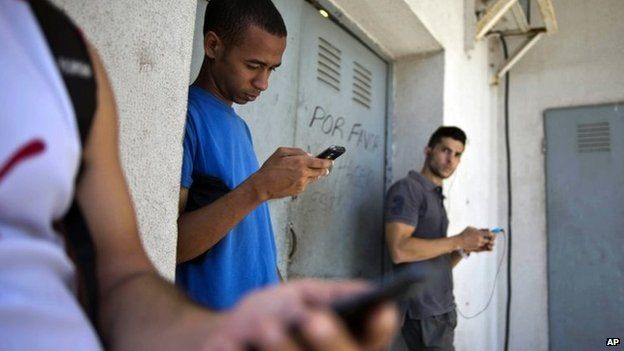 Students gather behind a business looking for a Internet signal for their smart phones in Havana, Cuba, 1 April 2014