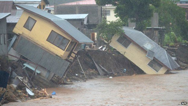 Flood waters run past damaged homes in the Solomon Islands capital of Honiara on 4 April 2014.