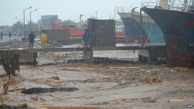 People walk past water clogged with debris at a port in the Solomon Islands capital of Honiara after flooding on 4 April 2014.