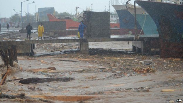 """People walk past water clogged with debris at a port in the Solomon Islands"""" capital Honiara"""