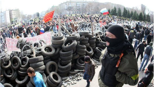 Pro-Russia activists guard a barricade set at the Ukrainian regional Security Service building in Donetsk on 7 April