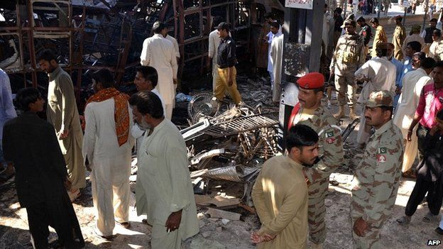 Pakistani security officials and local residents stand in shock after the bomb blast at Sibi station - 8 April 2014