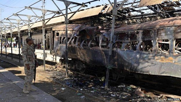 A soldier stands near a damaged passenger carriage at the site of a bomb blast at Sibi train station - 8 April 2014