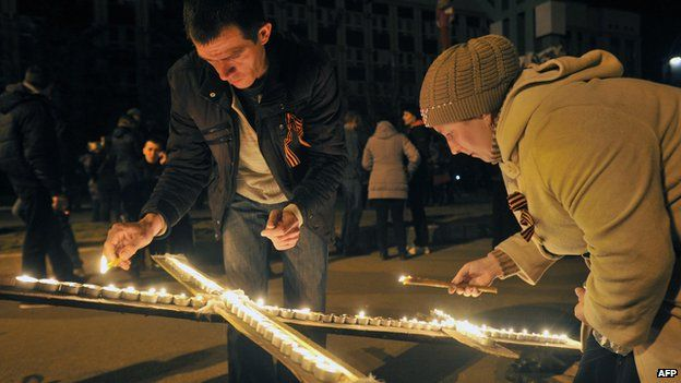 Pro-Russians light candles outside the regional Security Service building in Luhansk, eastern Ukraine, on 9 April 2014.