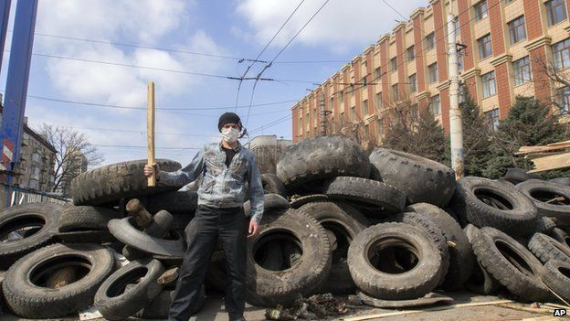A masked pro-Russian activist poses for a photo in front of barricades at the Ukrainian regional office of the Security Service in Luhansk,