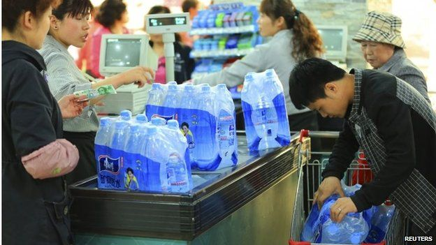 A man pushes a shopping cart filled with bottled water on Friday 11 April