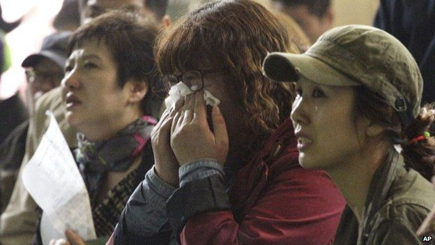 A mother weeps as she and others search for their children's names among a list of survivors