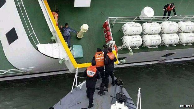 A passenger is rescued by South Korean maritime policemen from a sinking ship