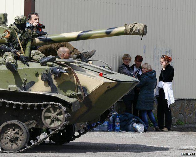 Women stand near soldiers wearing pro-Russian ribbons in Sloviansk, Ukraine, 16 April