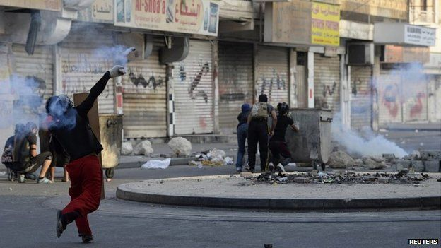 A protester throws a tear gas canister during clashes in Manama over the death of man detained by police - 27 February 2014
