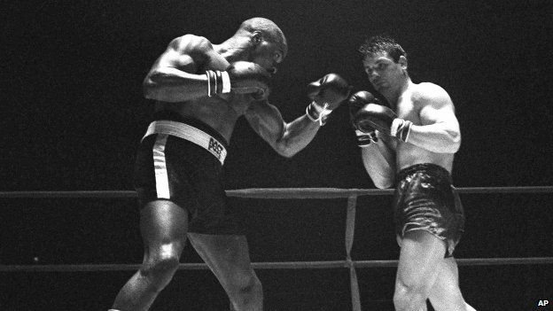 """File photo: Rubin """"Hurricane"""" Carter, left, knocks out Italian boxer Fabio Bettini in the 10th and last round of their fight at the Falais Des Sports in Paris, 23 February 1965"""