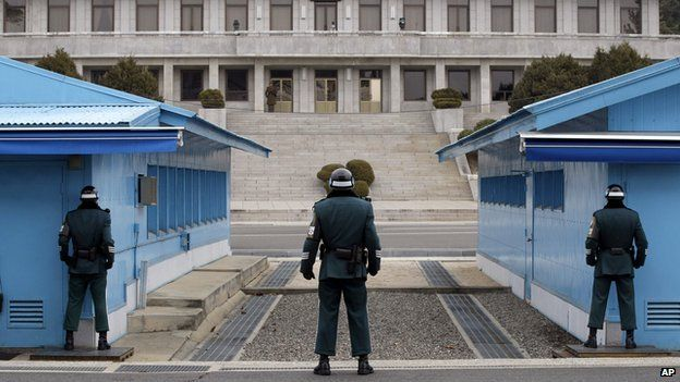 A North Korean soldier looks at the southern side as three South Korean soldiers guard at the border village of Panmunjom (South Korean side) on 12 March 2014.