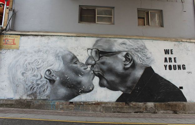 Graffiti on the street showing an elderly couple kissing