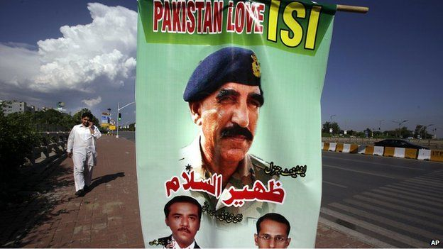 """A man walks past a banner showing a picture of Pakistan""""s Inter-Services Intelligence Chief Lt. General Zaheerul Islam, center, displayed by traders to show their support for the Pakistani army and ISI, in Islamabad, Pakistan, Saturday, April 26, 2014."""