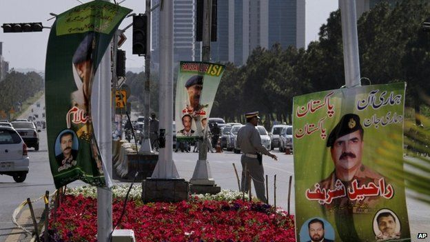 A police officer controls traffic next to a banner showing a picture of Pakistan's Inter-Services Intelligence Chief Lt Gen Zaheer Islam, centre, displayed by traders on main roads to show their support for the Pakistani army and ISI, in Islamabad, Pakistan, (26 April 2014)