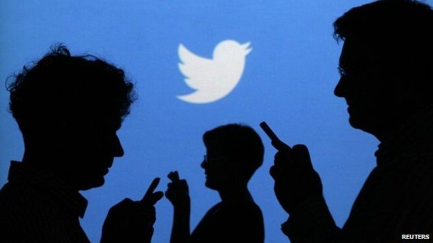 People holding mobile phones in front of the Twitter logo (27 September 2013)