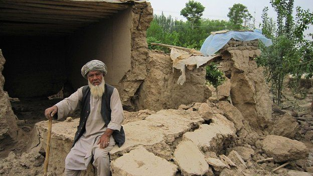 An Afghan man sits in front of his destroyed home