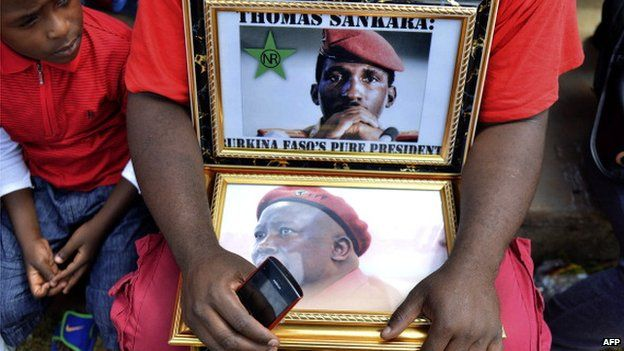 An EFF supporter holds portraits of former president of Burkina Faso Thomas Sankara and populist South African leader Julius Malema as he attends the launch of the EFF's manifesto in Thembisa on 22 February 2014