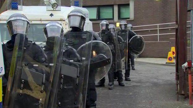 Police officers in riot gear alongside vans waiting to leave Antrim PSNI base