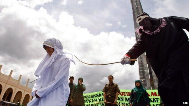 File photo: A woman is caned for violating Islamic sharia law outside a mosque in Jantho, Aceh province, Indonesia, 1 October 2010