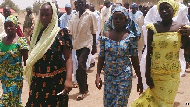 In this photo taken Monday 21 April 2014, four female students of the secondary girls' school in Chibok, who were abducted by gunmen and manged to escape, are reunited with their families walk in Chibok, Nigeria