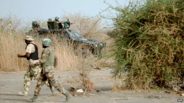 Nigerian soldiers patrol in the north of Borno state close to a Islamist extremist group Boko Haram former camp on 5 June 2013 near Maiduguri