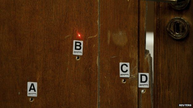 The red light from a laser lines up bullet holes on the bathroom door during the trial of Oscar Pistorius in Pretoria (12 May 2014)