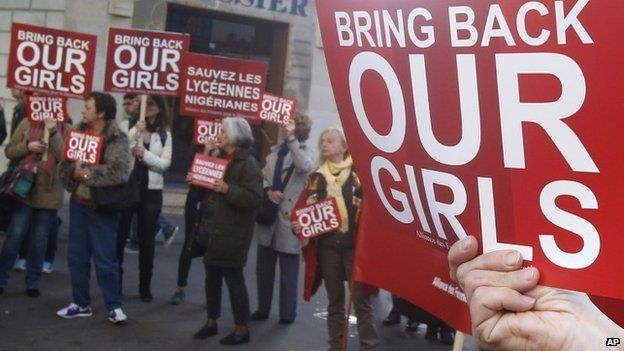 A woman holds a sign during a rally near the Nigerian embassy to raise to show support for the release of the kidnapped girls in Nigeria in Paris, Monday, May 12