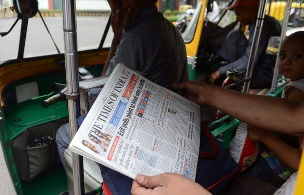 A commuter in an auto-rickshaw holds up a copy of an English-language Indian newspaper, with the headlines on exit polls
